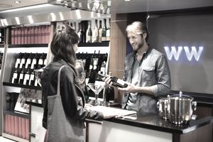 Sales clerk selling a wine bottle to a customer