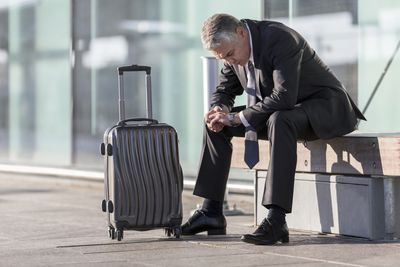 Businessman with graying hair waits with his luggage.r