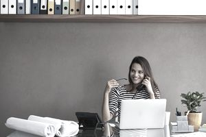 Woman on the phone sitting at her desk smiling