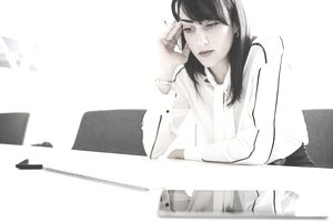 Stressed young businesswoman at office desk with notepad