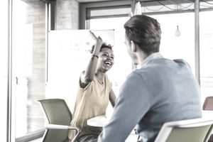 Happy young woman high fiving with colleague in office