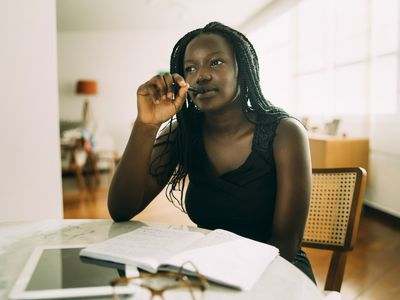 Woman using journal to help account for business transactions