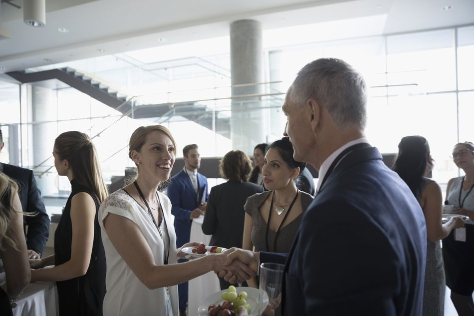 Business people handshaking, networking and eating at conference