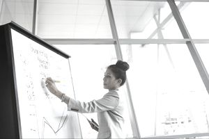 Businesswoman writing down financial measures on a whiteboard