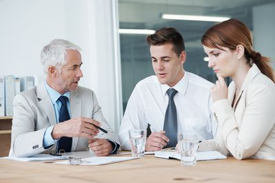 Two employees discussing strategy at a conference table with their superior.