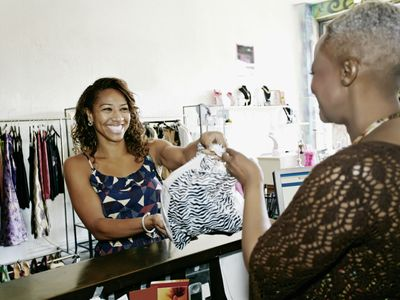 Smiling woman purchasing and paying for goods from a smiling retail clerk