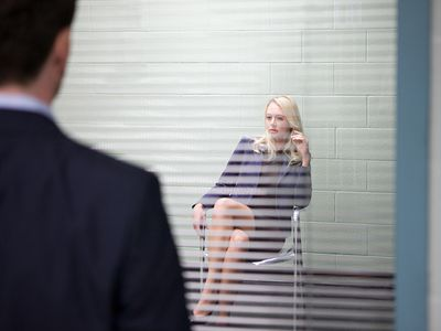 Woman sitting behind window with open blinds