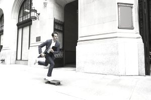 Businessman skateboarding on urban sidewalk