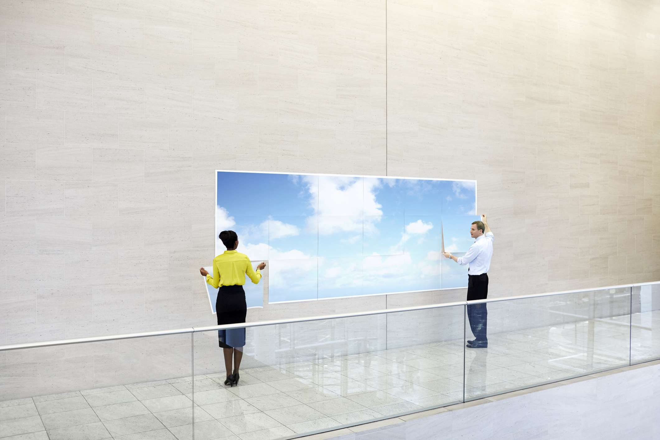 An sky and cloud art piece that looks like a large window created with large pieces of paper stuck to a wall