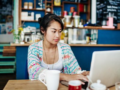Young Woman Working On Laptop In Colorful Coffee Shop