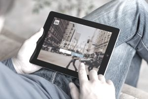 Man holding iPad with LinkedIn App on the screen