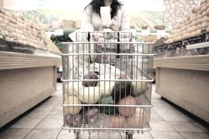 A woman holds her shopping list while leaning on her grocery cart in the produce aisle of the grocery store.