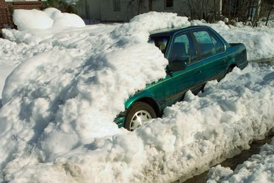 Car buried under a snow bank means someone will not be able to get to work.