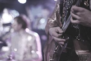 close up of a Man Playing Guitar with his manager standing in the background