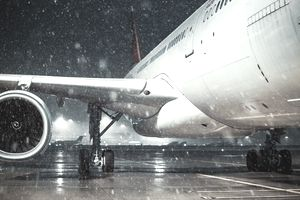 View of engine and fuselage of plane during a snowstorm
