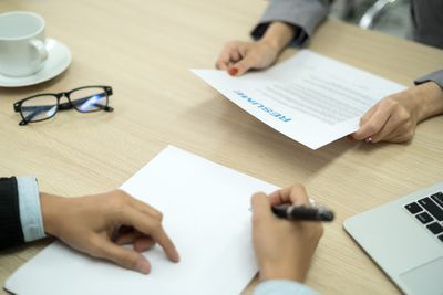 Business People Holding Resume On Table In Office