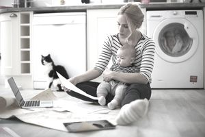 Woman holding baby son in arms, looking through work on kitchen floor
