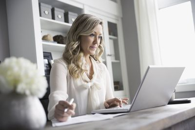 Woman working at laptop in home office