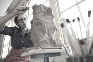 Artist working with a sculpture