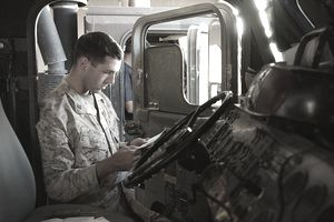 U.S. marine reading letter in truck cab