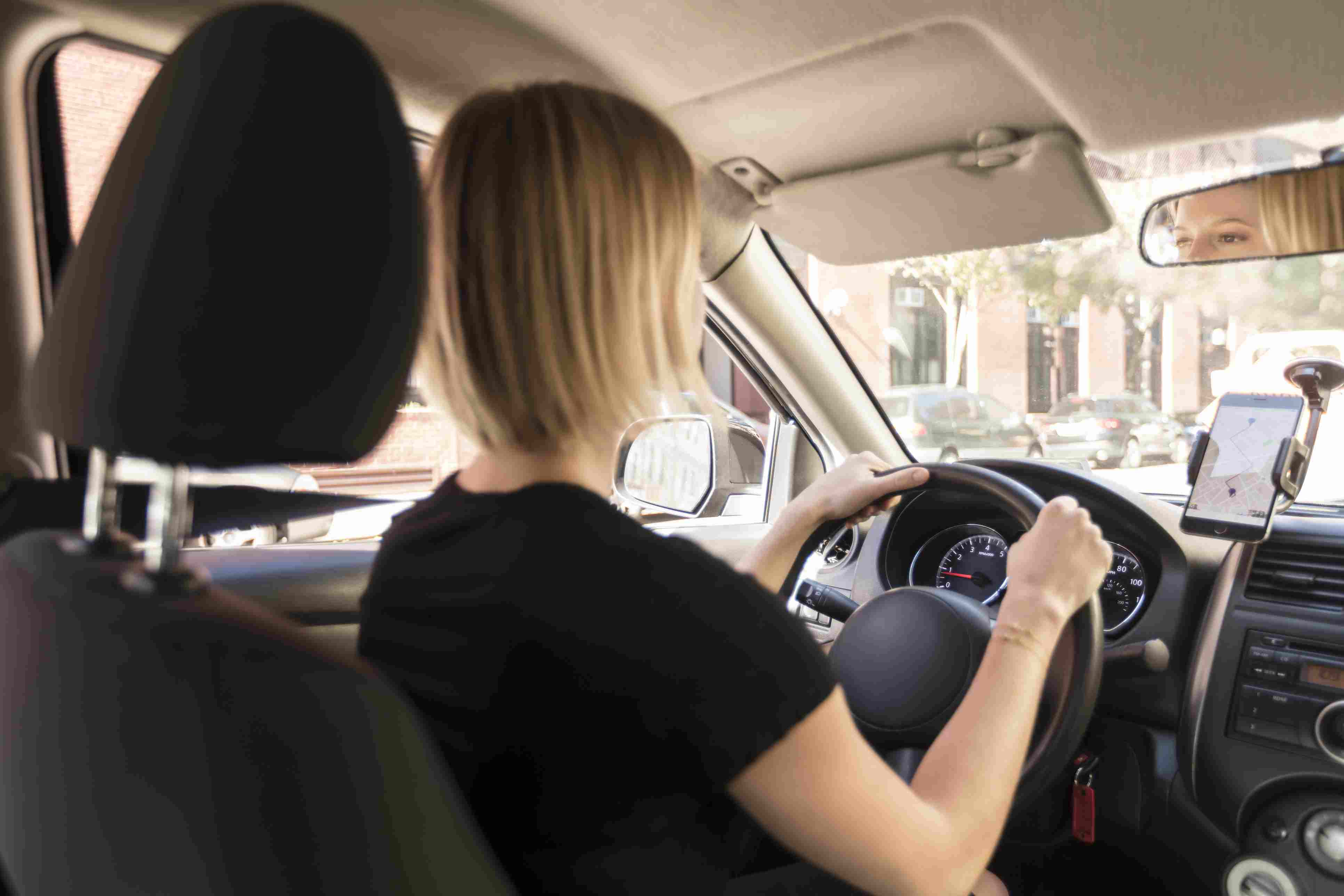 Woman behind the wheel of a car with a phone showing turn-by-turn directions mounted nearby.