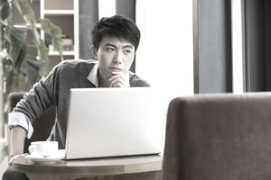 man thinking while at laptop