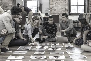 Members of an advertising agency sitting on the floor around head shots to choose a model