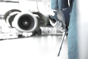 Worker holding tools in airport hangar