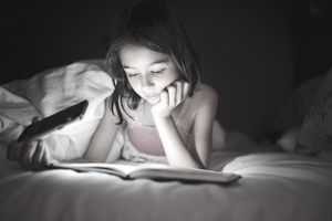 a young girl reading by cell phone light in bed