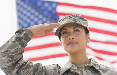 Female Army soldier saluting with the American flag in the background