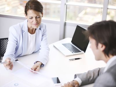 a female business person having a conversation with a young male associate