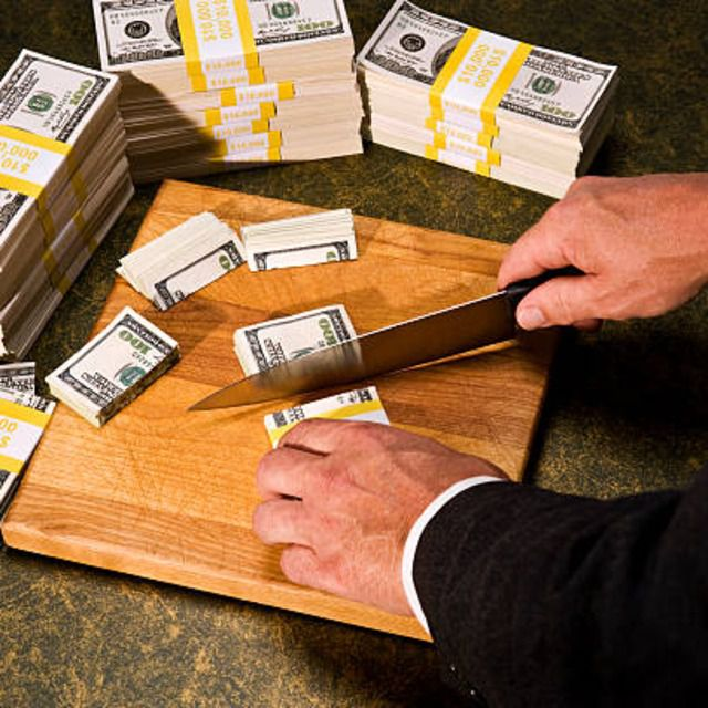Suited businessman budget cutting stacks of bills with sharp knife on a cutting board