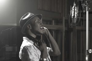 man singing in recording studio booth