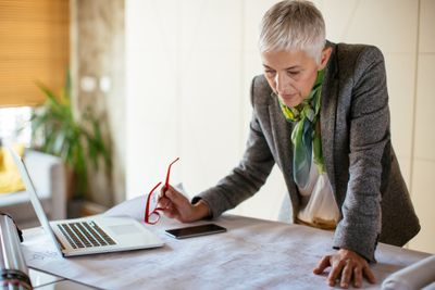 10 great jobs for retirees who want to go back to work mature female architect working on blueprint malvernweather Choice Image