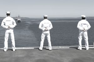 Sailors stand at parade rest as they man the rails aboard USS Essex as she leaves the port..