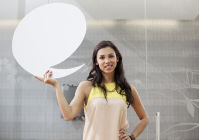 Woman standing with thought bubble cut out next to her head illustrating verbal communication