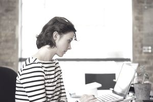 A young female employee works on laptop