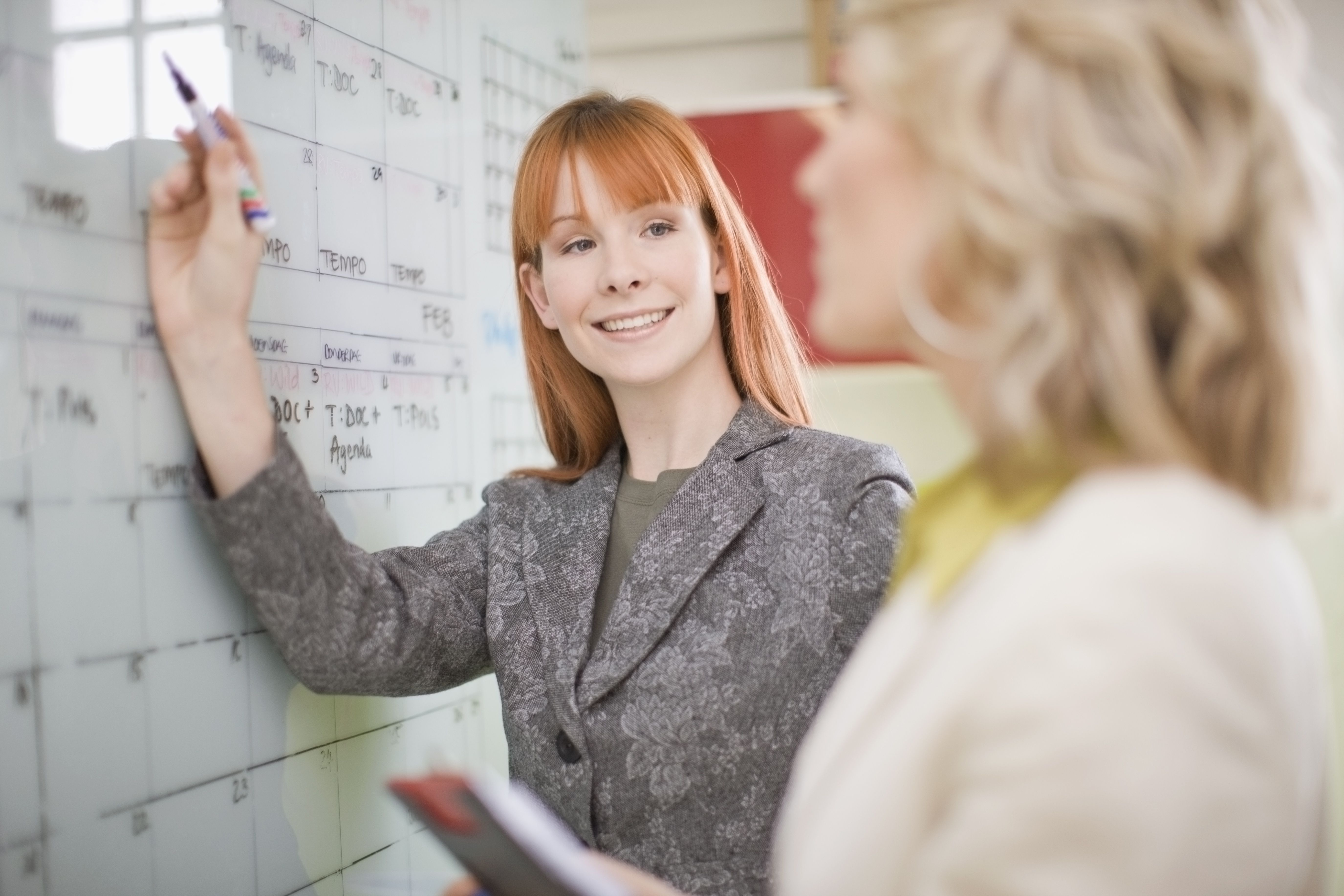 Businesswomen writing on a large wall planning calendar for future projects