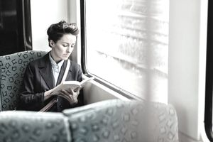 Business woman reading book on train