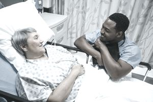 Licensed practical nurse talking to patient in hospital bed