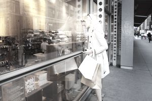 Woman looking at shop window with bags in hand