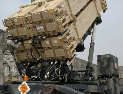 soldier performing a maintenance check on a Patriot missile launcher.