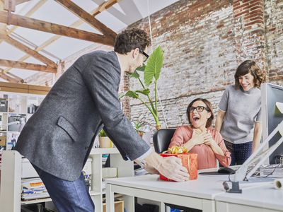 Man giving a gift to a woman sitting at her desk.