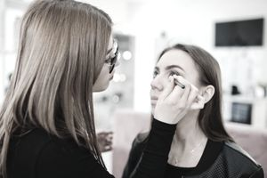 Beautician at work applying make up.