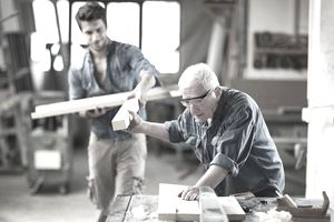 Construction helper handing a piece of wood to a carpenter working at a table saw in a shop.