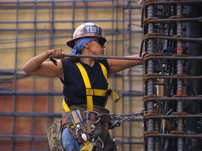 Woman wearing a hard hat, safety gear and a tool belt working with rebar.