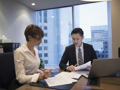 Lawyers reviewing contract at laptop in conference room meeting