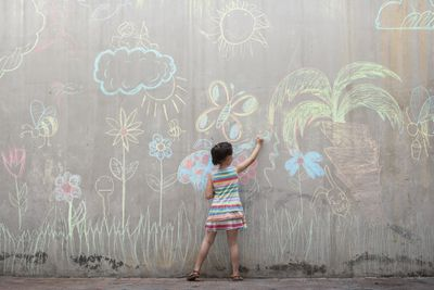 Girl drawing flowers on a concrete wall, representing the concept of optimism.