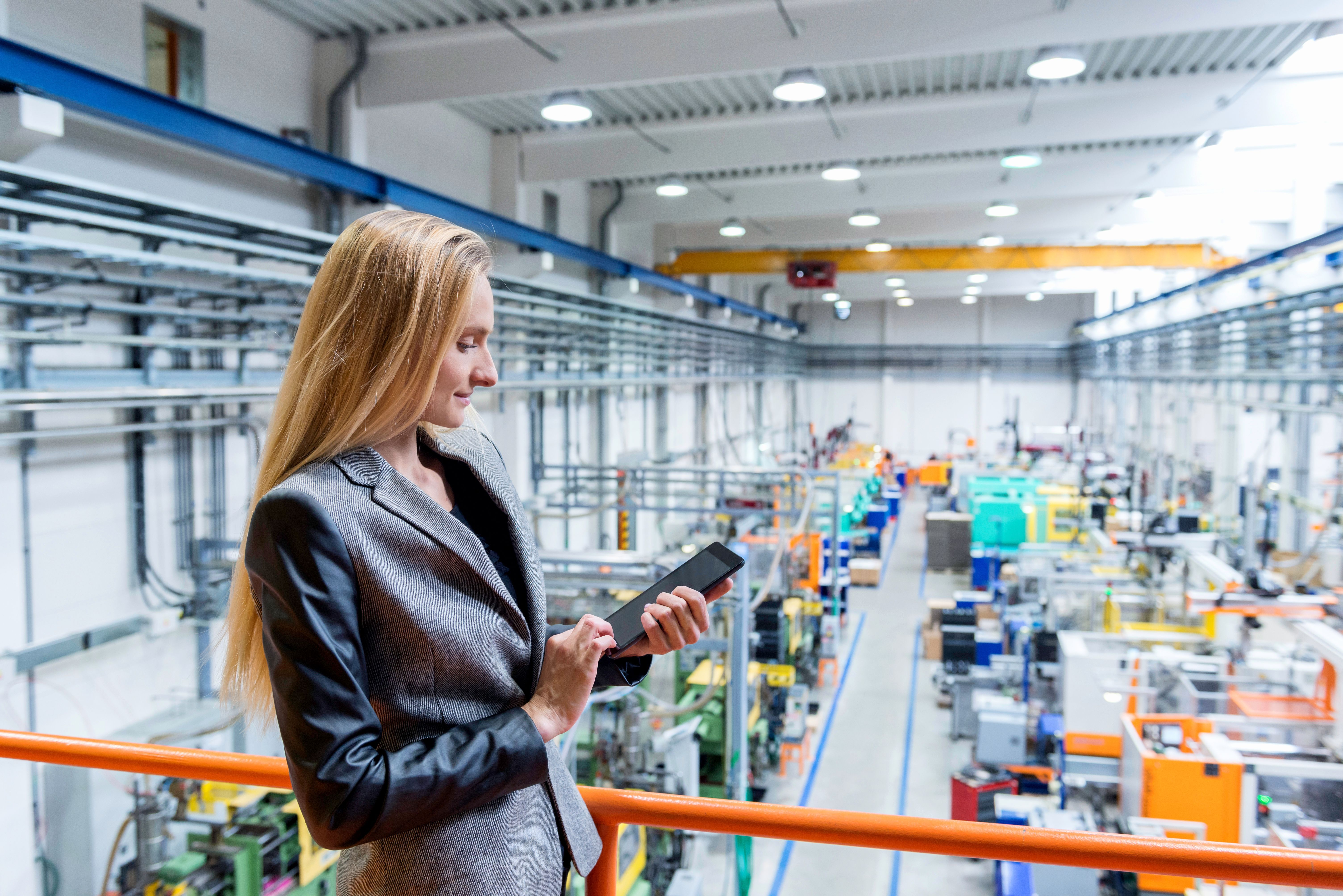 Professional female worker with tablet in futuristic factory