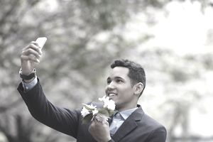 Man with flowers taking a picture with a phone